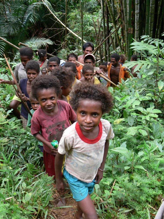 A group of Indonesians, mainly children, in a forest