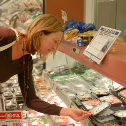 Clare Perry in a Japanese supermarket holding a plastic packaging.