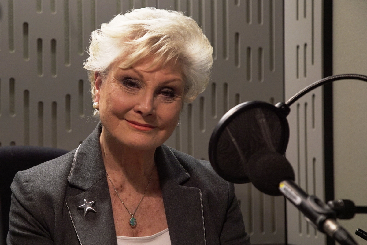 Angela Rippon sitting in front of a microphone in a BBC recording studio