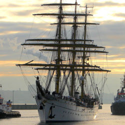 Traditional Germany Navy training vessel the Gorch Fock in the water straddled by two barges