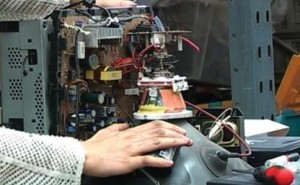EIA investigator installing a tracking device in a broken monitor to follow illegal e-waste shipments (c) EIA