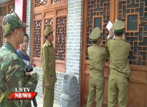 Officials seal a business in the raid on the GT SEZ, screengrab via Laos National TV