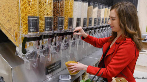 A shopper in Waitrose filling a reusable container with pasta