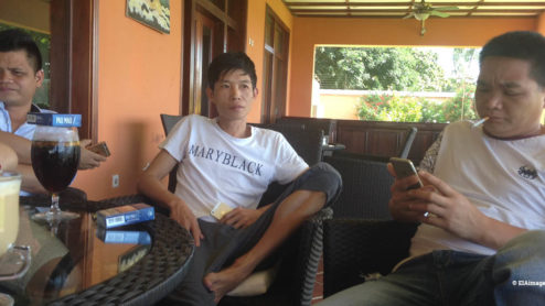 Three Chinese men meeting in a terrace in Mozambique