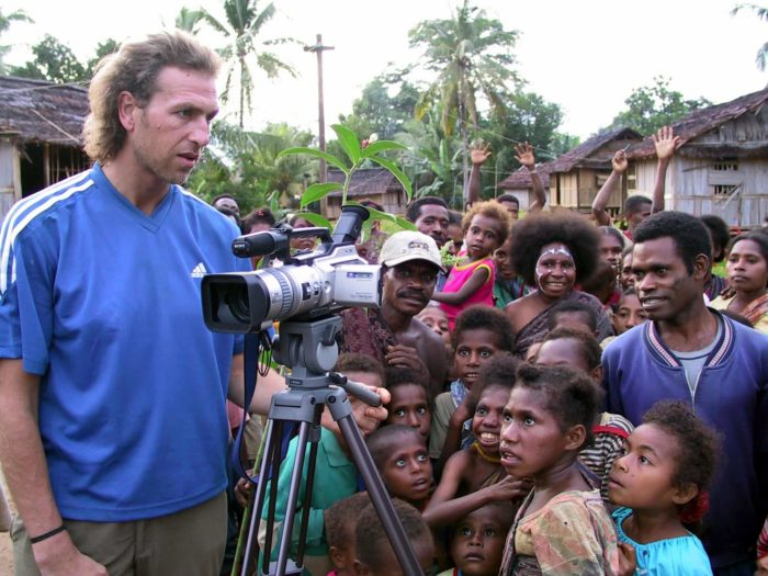Julian Newman with a filming camera and a group of people in an Indonesian village