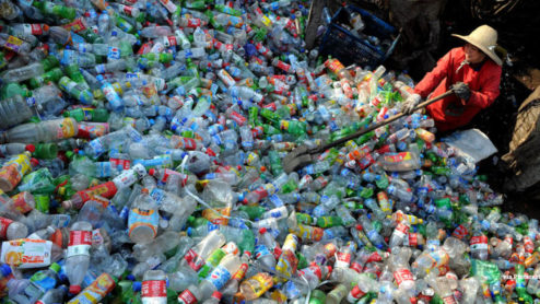 A woman sifts through a Pile of Plastic waste collected for processing