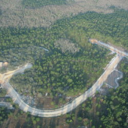 An aerial view of a forest intersected by a road