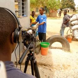 A cameraman filming local people cooking in Tanzania